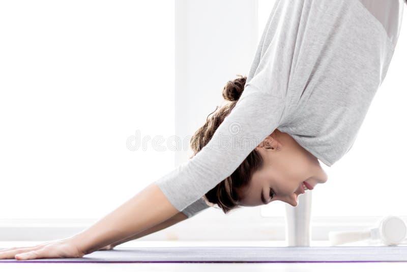 Ung kvinna som hemma g?r yogagenomk?rare fotografering för bildbyråer