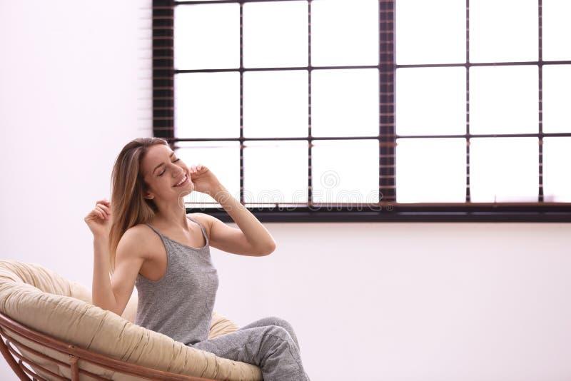 Ung kvinna som hemma kopplar av n?ra f?nster med rullgardiner fotografering för bildbyråer