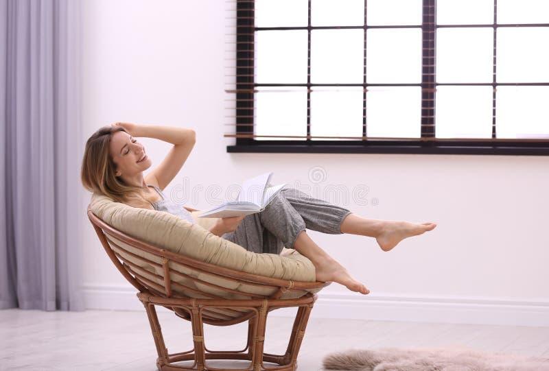 Ung kvinna som hemma kopplar av n?ra f?nster med rullgardiner royaltyfri fotografi