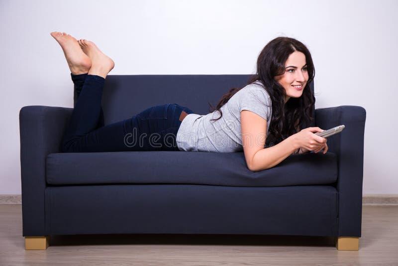 Ung kvinna som hemma ligger på soffan och hållande ögonen på tv fotografering för bildbyråer