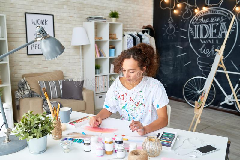 Ung kvinna som hemma målar arkivbilder