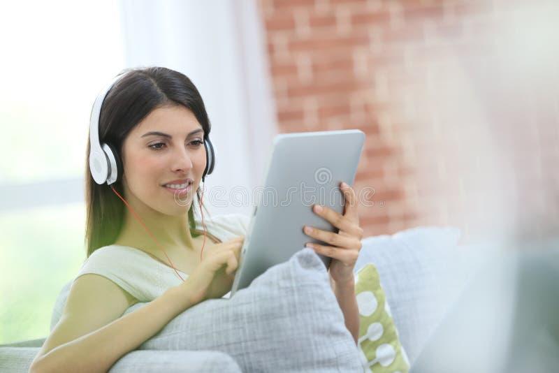 Ung kvinna som hemma sitter genom att använda minnestavlan royaltyfria foton