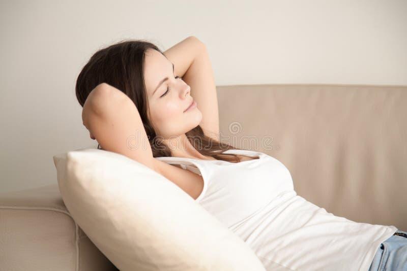 Ung kvinna som hemma vilar på den bekväma soffan arkivfoton