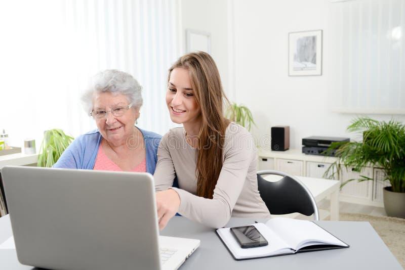 Ung kvinna som hjälper en gammal hög kvinna som hemma gör skrivbordsarbete och handläggningsrutiner med bärbar datordatoren arkivfoto