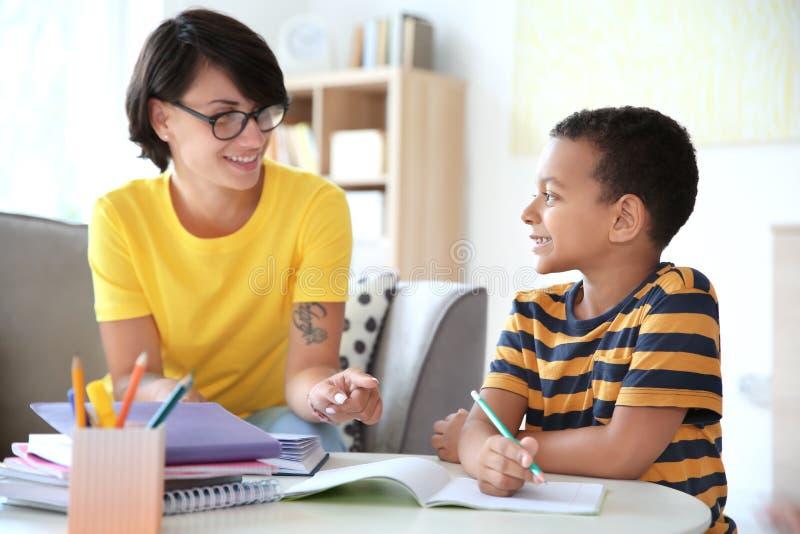 Ung kvinna som hjälper hennes barn med läxa arkivbilder