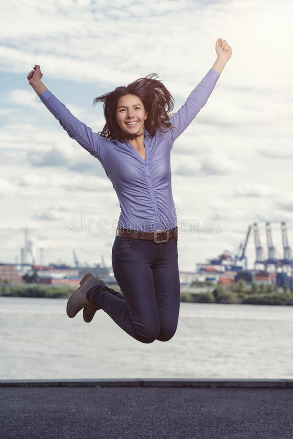 Ung kvinna som hoppar och hurrar för glädje royaltyfri bild