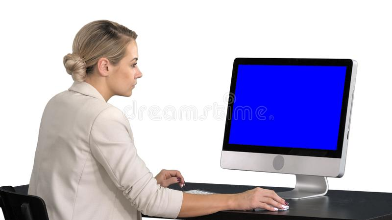 Ung kvinna som i regeringsställning arbetar och att sitta på skrivbordet som ser bildskärmen, vit bakgrund Blue Screen modellskär royaltyfria foton
