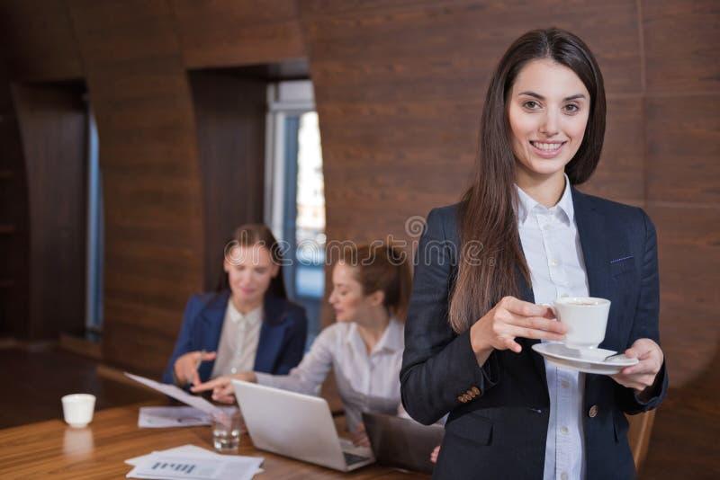 Ung kvinna som i regeringsställning poserar med hennes kollegor royaltyfri fotografi