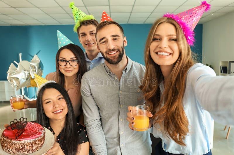Ung kvinna som i regeringsställning tar selfie med hennes kollegor på födelsedagpartiet royaltyfri bild