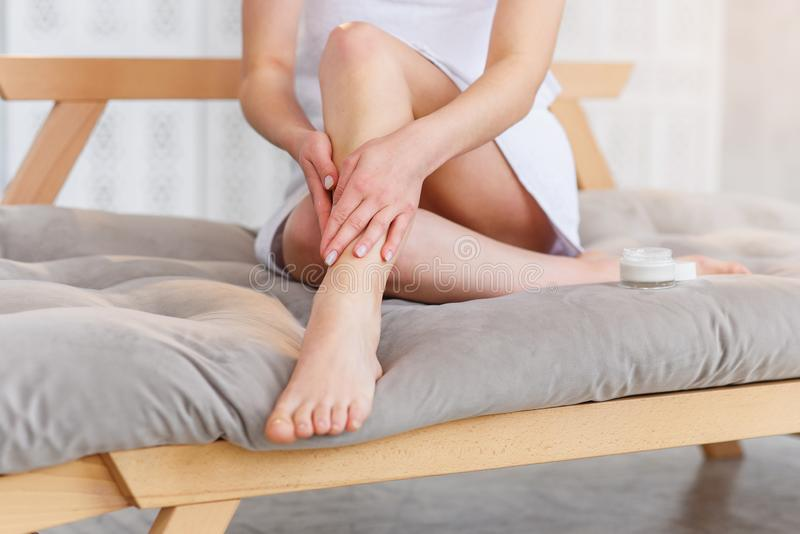 Ung kvinna som inomhus applicerar kroppkräm på hennes ben med slät mjuk hud, closeup Sk?nhet och f?rkroppsligar omsorg royaltyfria bilder