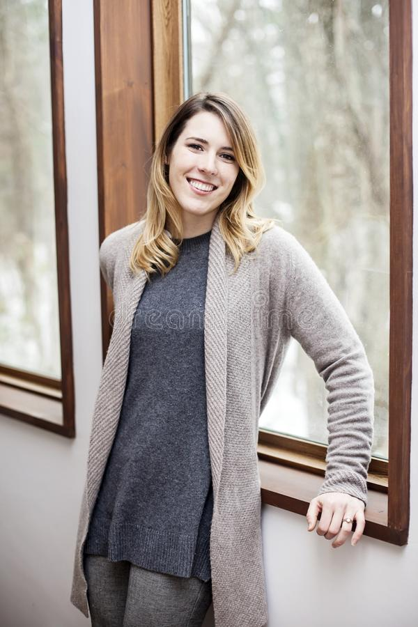 Ung kvinna som inomhus kopplar av i vinter royaltyfri fotografi