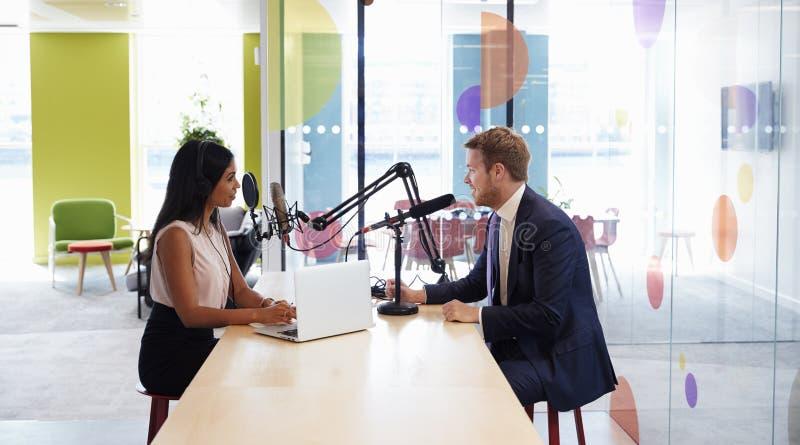 Ung kvinna som intervjuar en gäst i en studio för en podcast royaltyfri foto