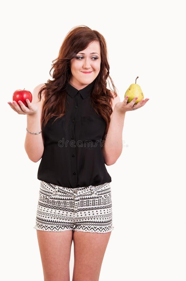 Ung kvinna som jämför ett äpple och ett päron som försöker att avgöra vilket arkivfoto