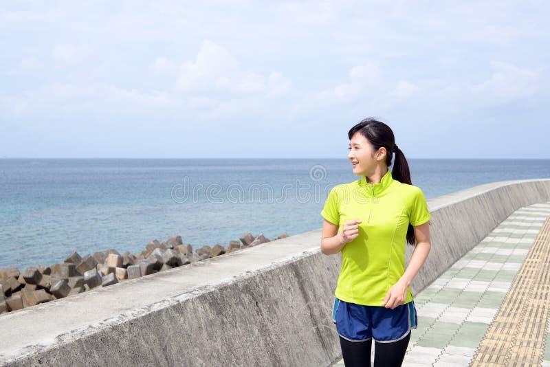Ung kvinna som joggar förbi havet arkivbild