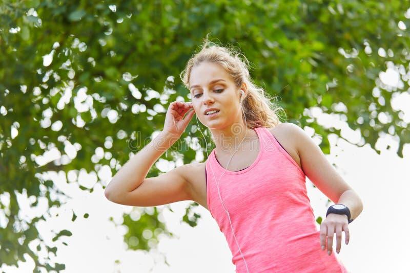 Ung kvinna som joggar med smartwatch arkivfoto