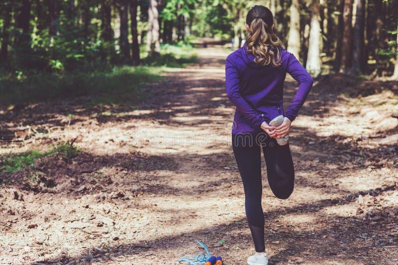 Ung kvinna som joggar och gör övningar i den soliga skogen arkivfoto