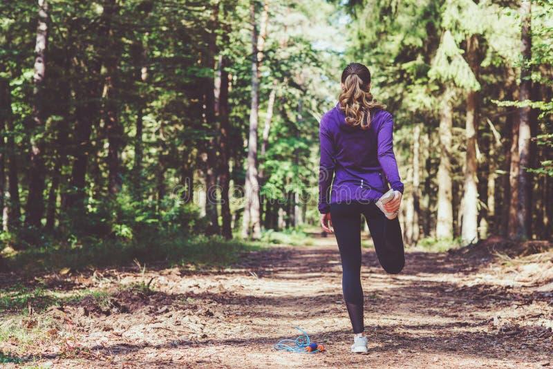 Ung kvinna som joggar och gör övningar i den soliga skogen royaltyfri bild