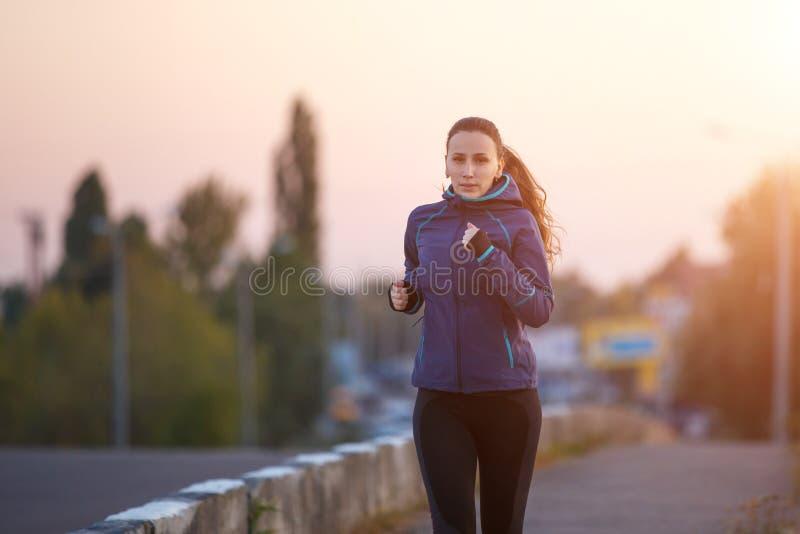 Ung kvinna som joggar på bron i otta arkivfoto