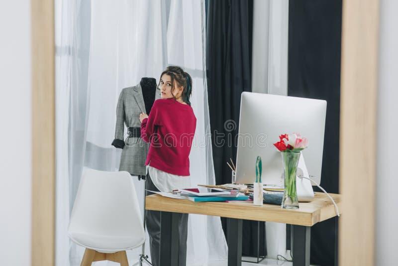 Ung kvinna som justerar dräkten på skräddareattrapp på modernt royaltyfri fotografi