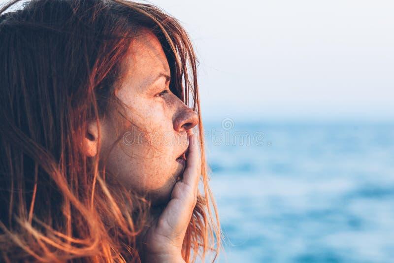 Ung kvinna som känner sig ledsen på pir arkivfoton