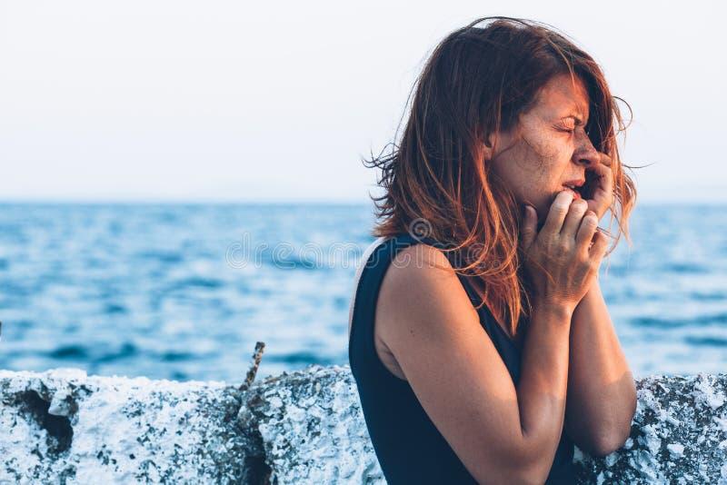 Ung kvinna som känner sig ledsen på pir royaltyfri bild