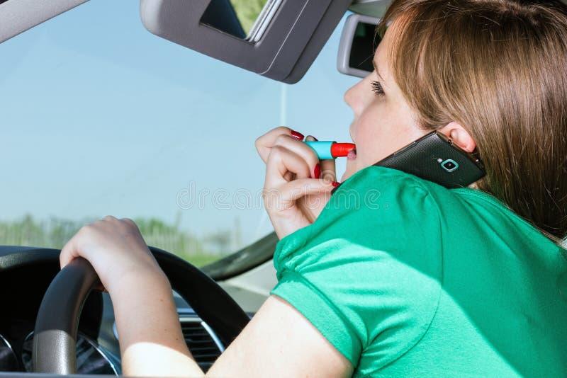 Ung kvinna som kör, applicerar läppstift och talar på henne som är smar royaltyfri bild