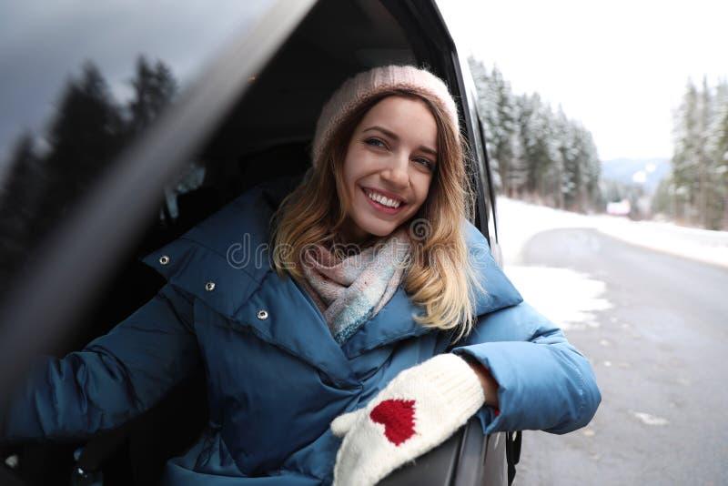 Ung kvinna som kör bilen och ser ut ur fönster snowman för sand för hav för bakgrundsstrand exotisk gjord tropisk semester vit vi arkivfoton
