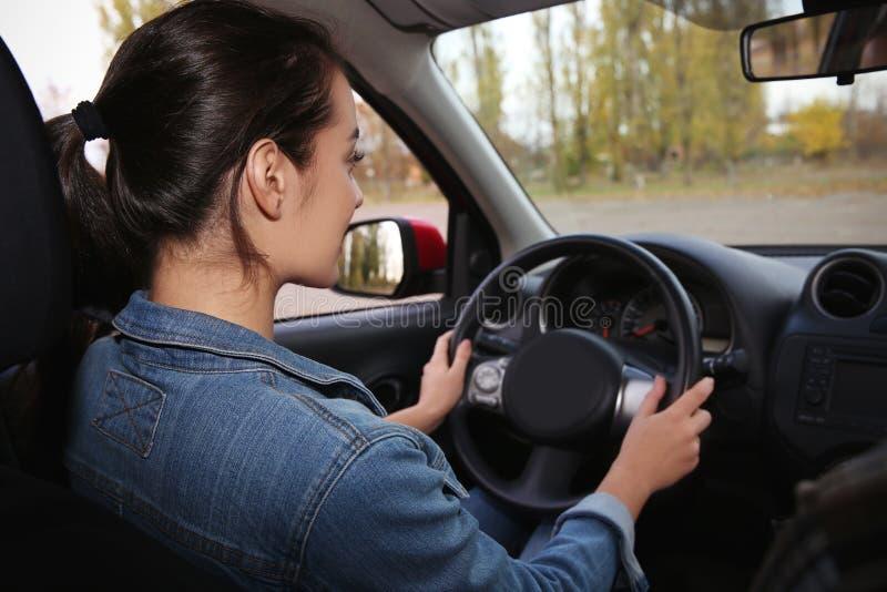 Ung kvinna som kör bilen på vägen royaltyfria foton