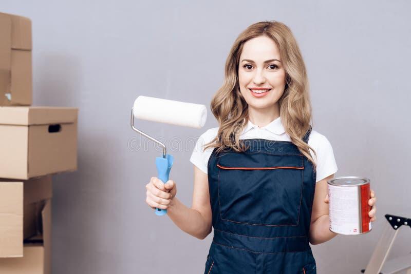 Ung kvinna som kör en husmålare En kvinna är förlovad, i att måla väggarna royaltyfri fotografi