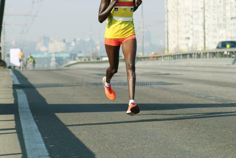 Ung kvinna som k?r p? stadsbrov?gen Maratonspring i morgonljuset K?ra p? stadsv?gen K?ra f?r idrottsman nenl?parefot royaltyfri bild