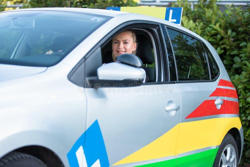 Ung kvinna som kör studenten som sitter i en bil royaltyfri bild