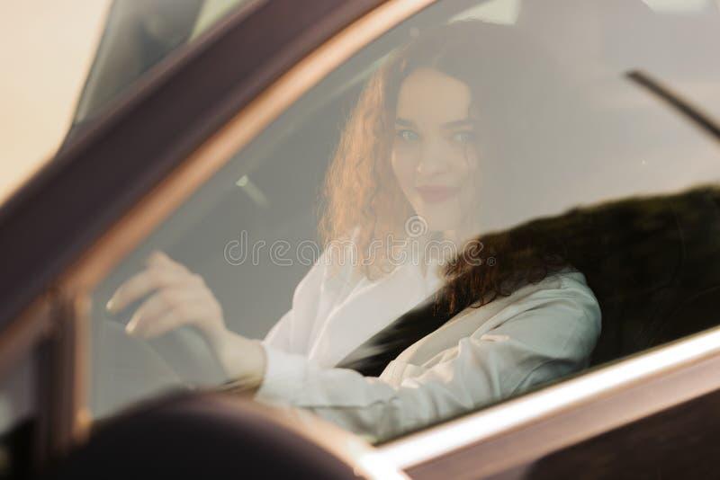 Ung kvinna som k?r en bil i staden St?ende av en h?rlig aff?rskvinna i en bil ?gander?tt f?r home tangent f?r aff?rsid? som guld- arkivbild