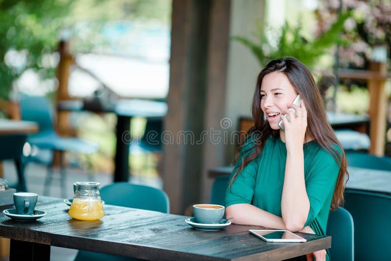Ung kvinna som kallar med celltelefonen, medan sitta bara i coffee shop under fri tid Attraktiv kvinnlig med gulligt arkivfoton