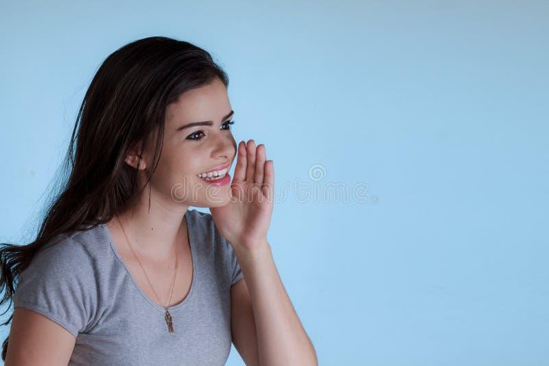Ung kvinna som kallar någon med en hand bredvid munnen arkivbilder
