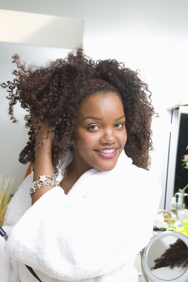 Ung kvinna som kammar hår royaltyfria bilder