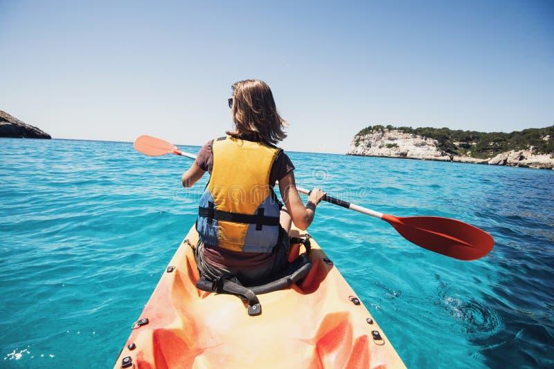 Ung kvinna som kayaking i havet Aktivt livsstil och loppbegrepp fotografering för bildbyråer