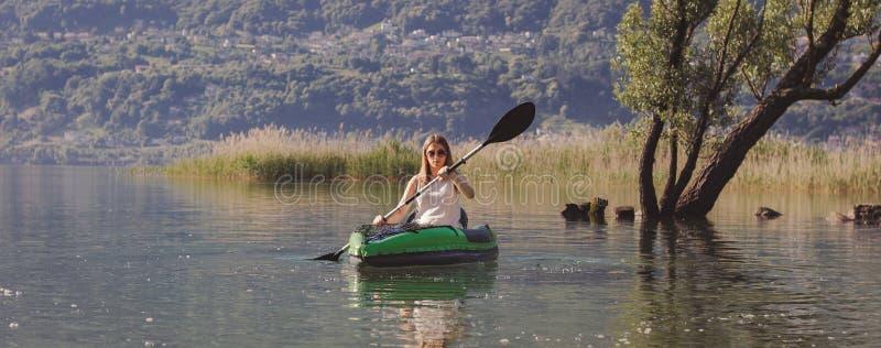 Ung kvinna som kayaking på sjön arkivfoton
