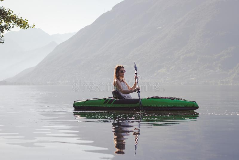 Ung kvinna som kayaking p? sj?n royaltyfri fotografi