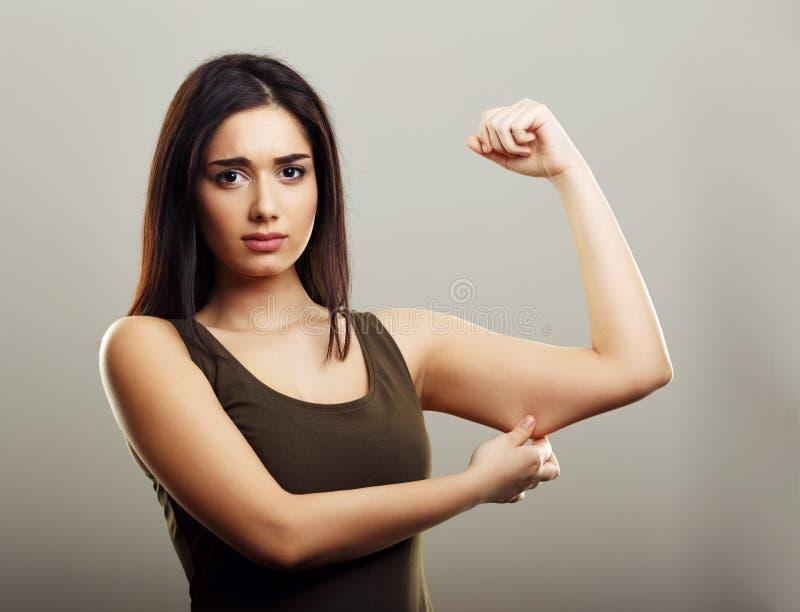 Ung kvinna som klämmer fet hud för arm royaltyfri bild