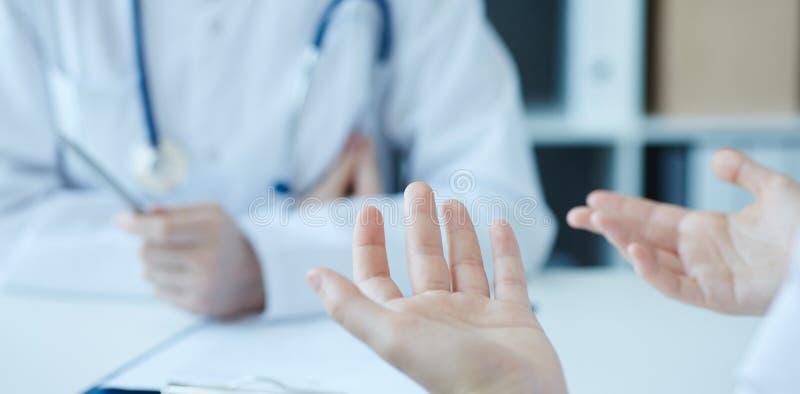 Ung kvinna som konsulterar med läkarundersökningen som doctorcomplaining om hälsa och att ha problem Fokus på tålmodiga händer fö arkivfoton