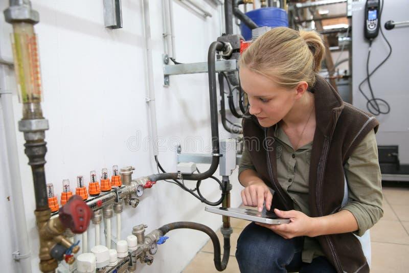 Ung kvinna som kontrollerar vattennivån royaltyfri fotografi