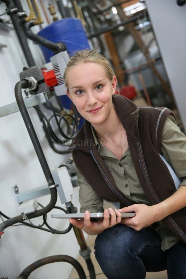 Ung kvinna som kontrollerar vattennivån i plumbery arkivbild