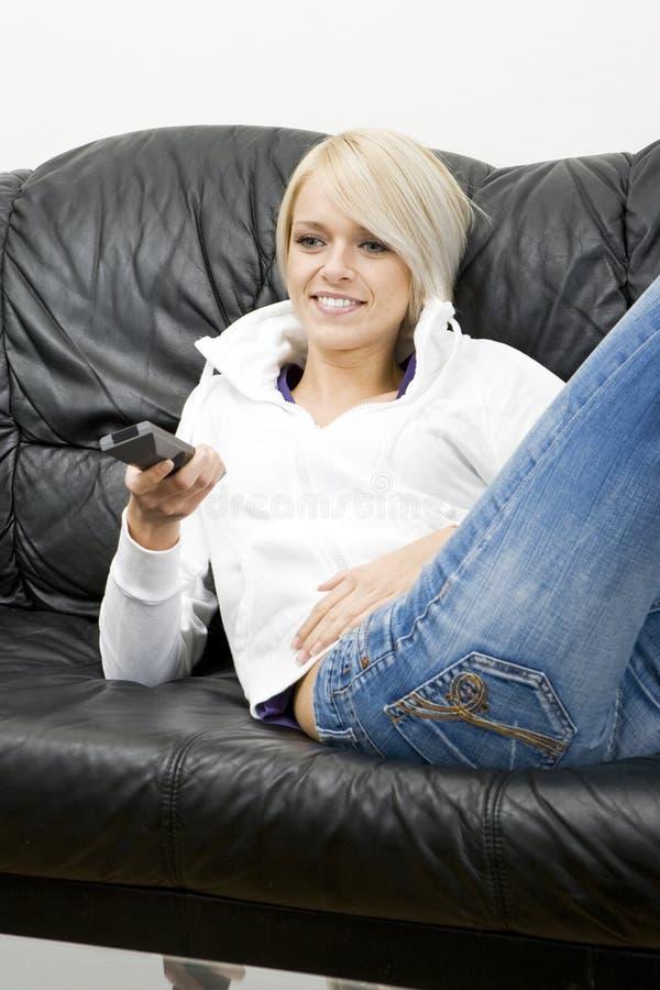 Ung kvinna som kopplar av hållande ögonen på television arkivfoto