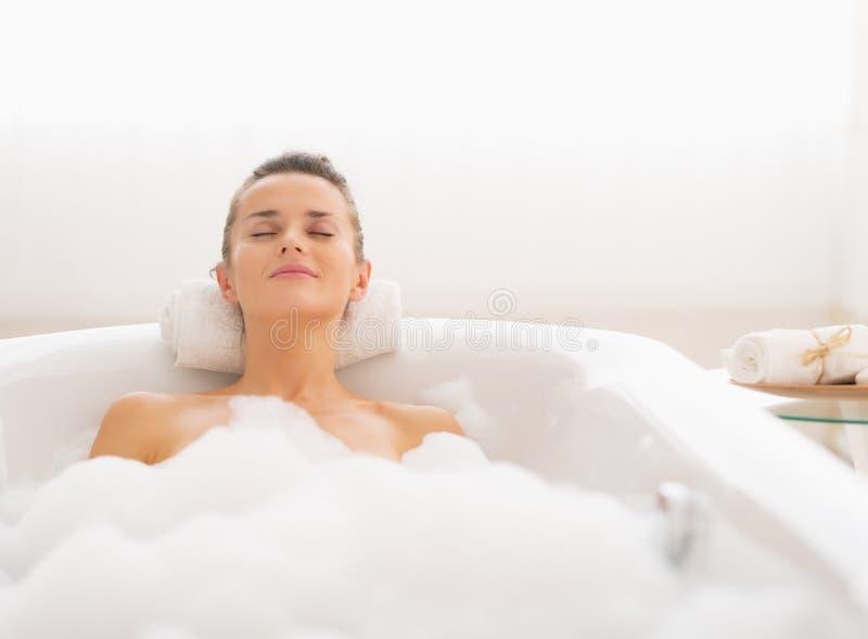 Ung kvinna som kopplar av i badkar fotografering för bildbyråer