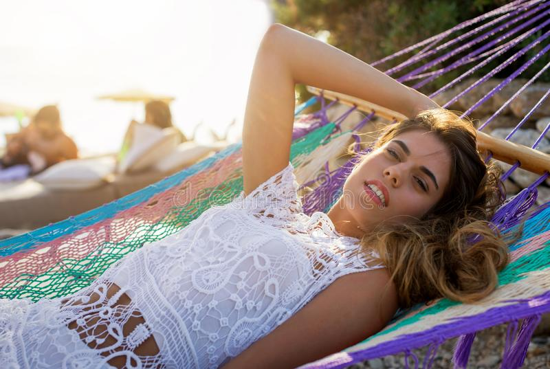 Ung kvinna som kopplar av i en hängmatta på en strand under sommartid fotografering för bildbyråer