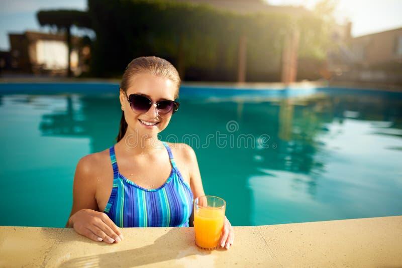 Ung kvinna som kopplar av i en pöl i sommar med exponeringsglas av orange fruktsaft Nätt caucasian blond flicka som bär den blåa  royaltyfri fotografi