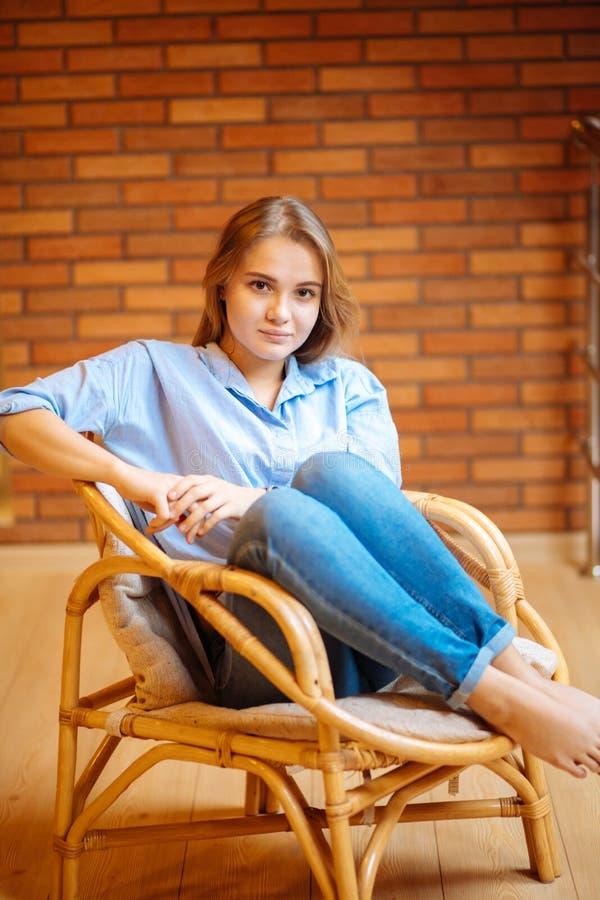 Ung kvinna som kopplar av i en stor bekväm stol fotografering för bildbyråer