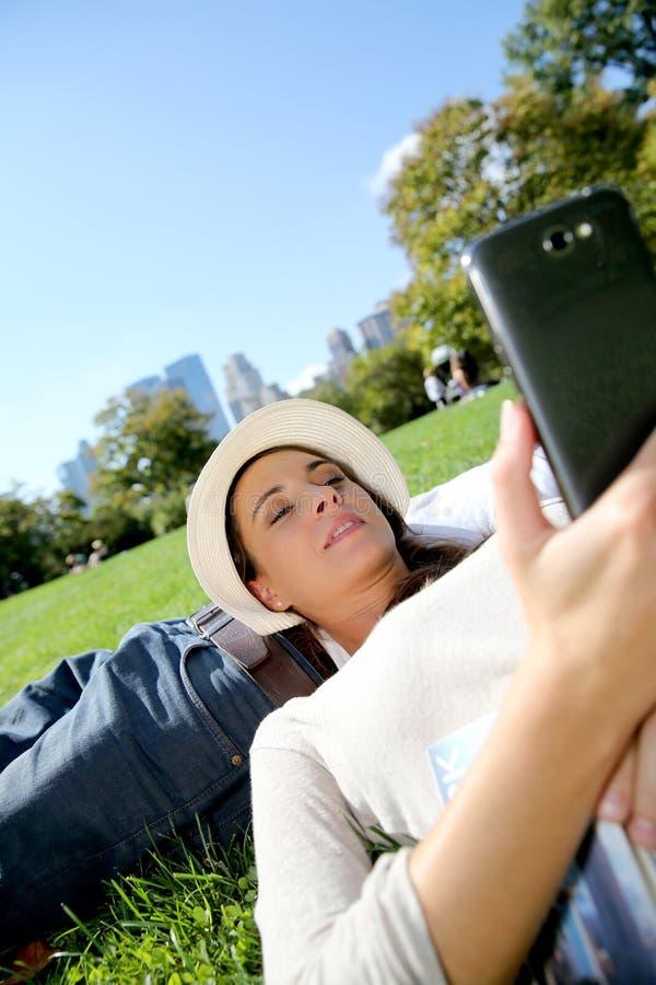 Ung kvinna som kopplar av i gräs genom att använda smartphonen royaltyfria bilder