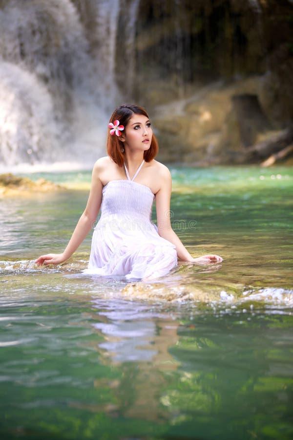 Ung kvinna som kopplar av i vattenström royaltyfri bild