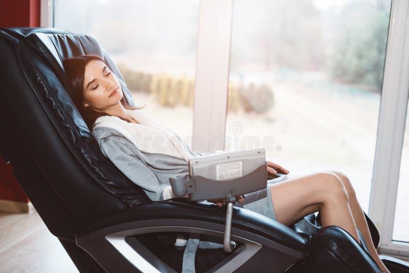 Ung kvinna som kopplar av på den massera stolen arkivfoto